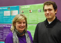 Jane Stanford-Beale and Conor Eldred-Earl in front of the Autism in Berkshire: Past and Present exhibition panel featuring Conor